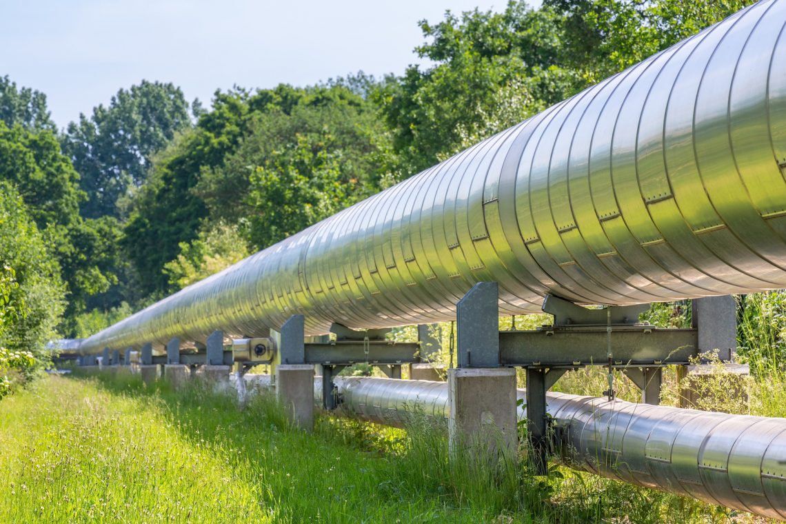 Huge metal gas pipeline distributing gas outside. In the Netherlands they extract gas as energy out of the ground. It is distributed above the ground through large and long gas pipelines like you see here. The dutch government is planning to stop the use of gas for the dutch households and also for the industry. Using electric energy will be better for our natural environment.